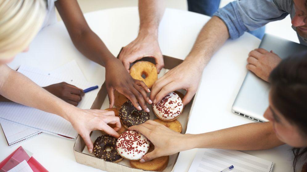Foto: Unas personas cogen unos dulces de una caja. (iStock)
