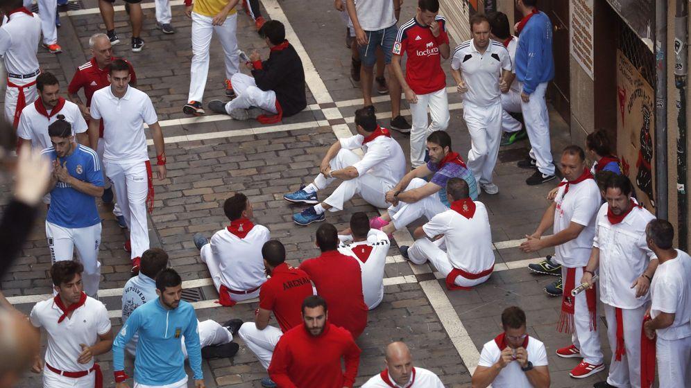 Foto: Varios mozos protestan minutos antes del quinto encierro. (EFE)