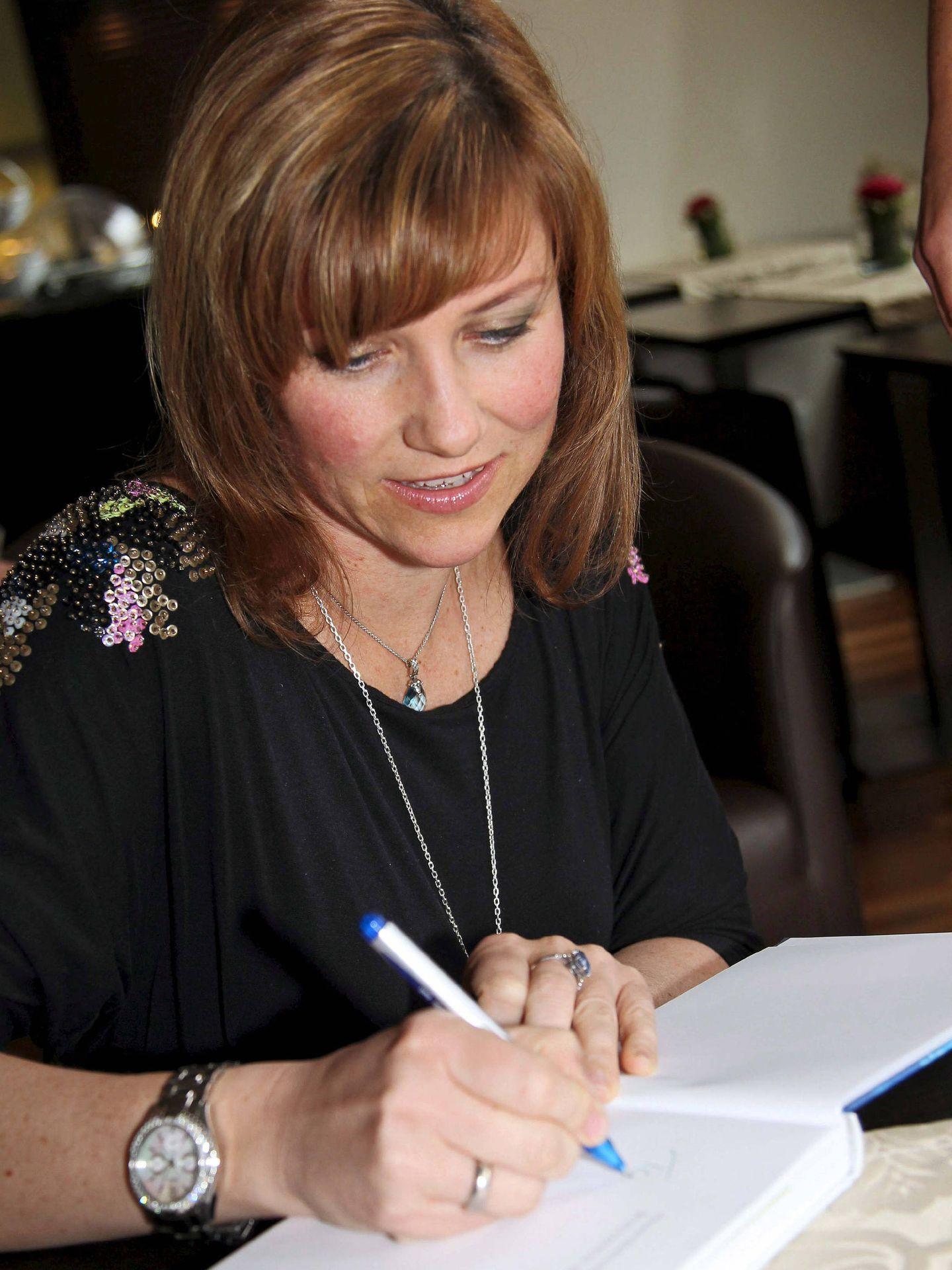 La princesa, firmando uno de sus libros.  (EFE)
