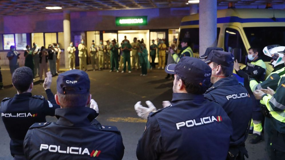 Foto: Varios policías nacionales y guardias civiles aplauden en Santiago de Compostela al personal de urgencias del hospital Clínico. (EFE)