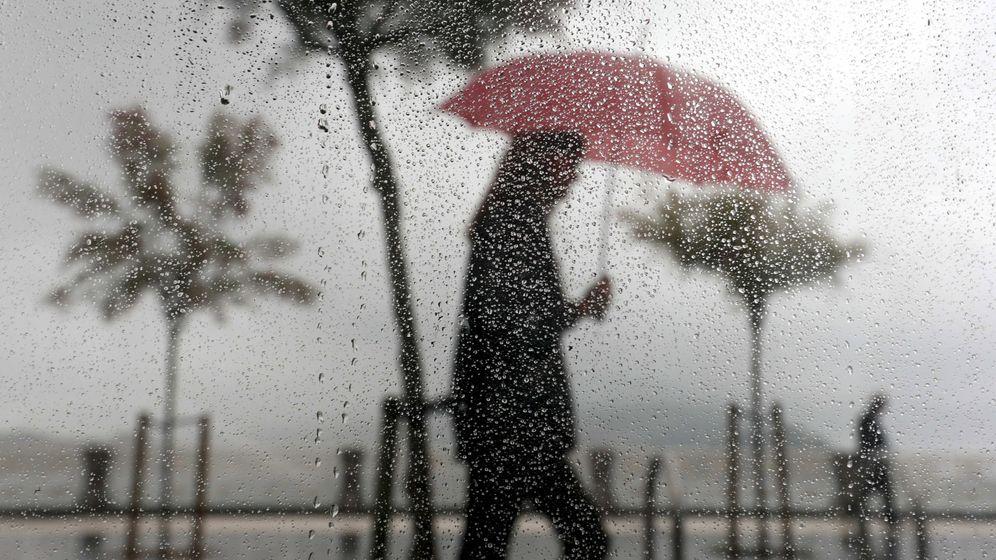 Foto: Una mujer camina bajo la lluvia en el paseo de la Concha de San Sebastián. (EFE)