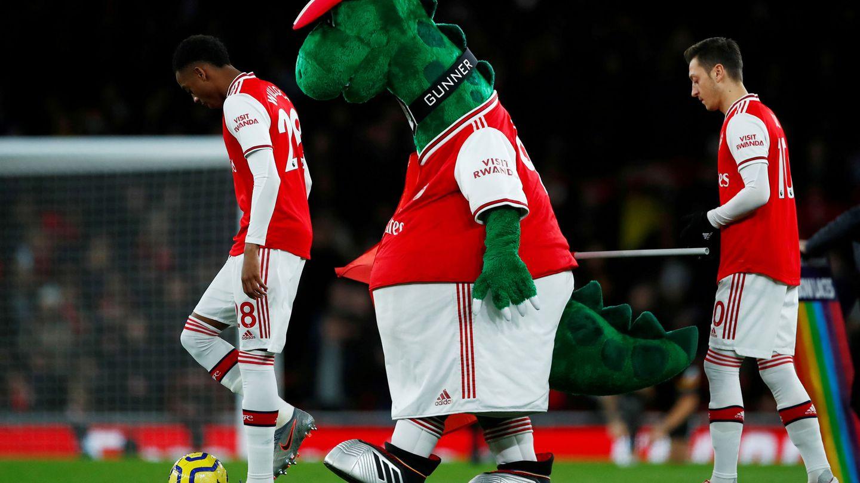 La mascota del equipo, con Ozil a su espalda. (Reuters)