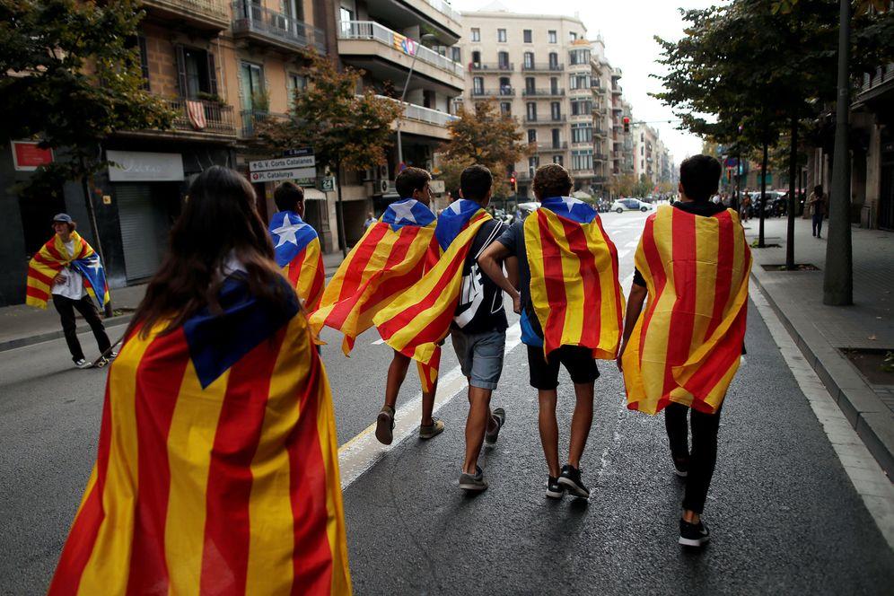 Foto: Unos jóvenes pasean con banderas esteladas durante la jornada de huelga general en Barcelona. (Reuters)
