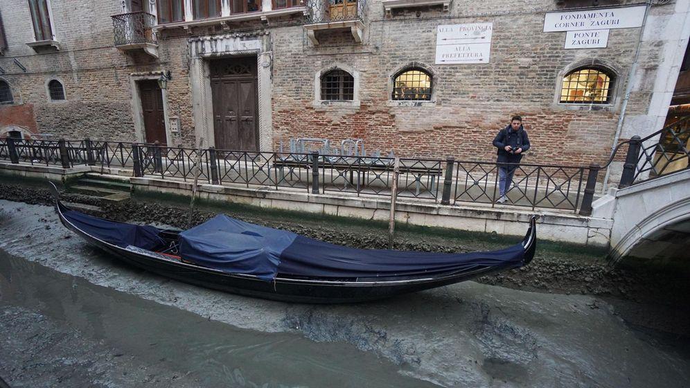 Foto: Una góndola permanece amarrada en un canal prácticamente sin agua en Venecia. (Efe)
