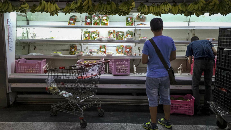 Clientes buscan alimentos en un supermercado con estanterías parcialmente vacías, con vistas al parón de 48 horas convocado por la oposición a partir del miércoles. (EFE)
