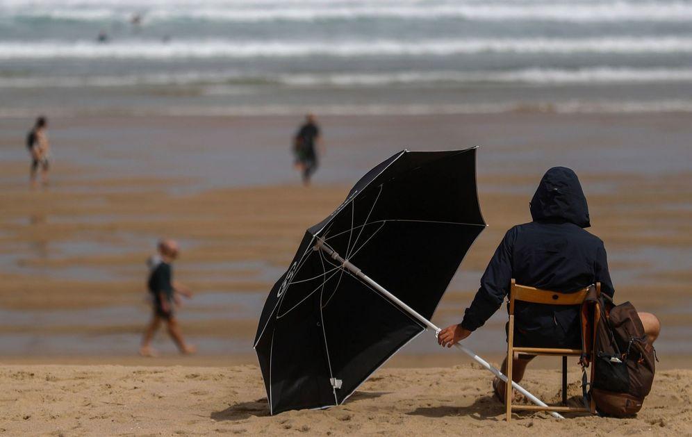 Foto: Un joven se protege del sol en la playa de la Zurriola de San Sebastián este mes de junio. (EFE)