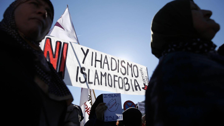 Dos mujeres, cerca de un cartel que reza 'Ni islamofobia ni yihadismo' durante una manifestación en la estación de Atocha, Madrid. (Reuters)