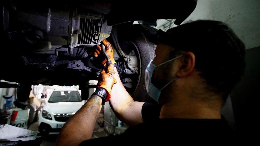 Foto: Un mecánico trabaja, con mascarilla, en un taller en Madrid. (EFE)