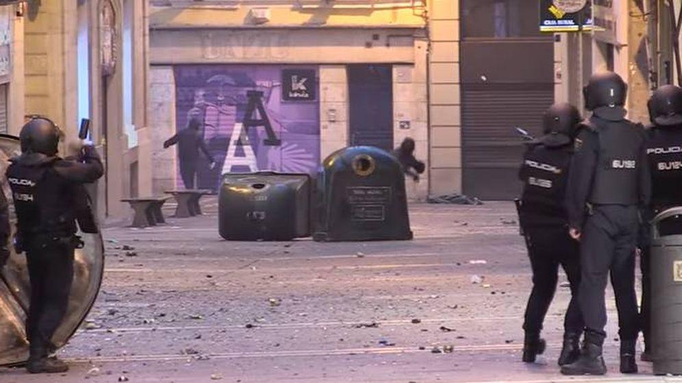 Foto: Encapuchados lanzan objetos a la policía, en Pamplona. (YouTube)