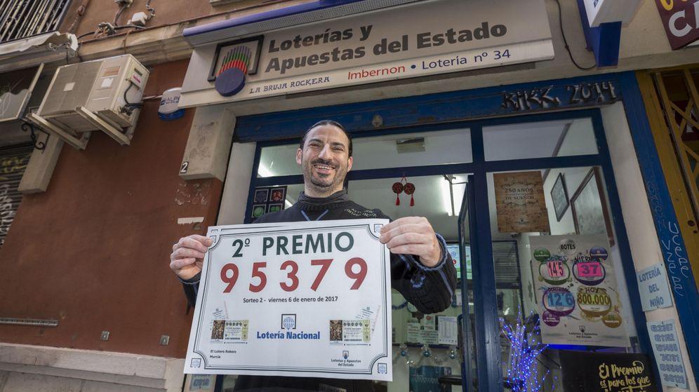 Foto: El gerente de la administración de loterias La Bruja Rockera, la número 34 de Murcia, José María Imbernon, muestra el cartel del segundo premio del sorteo del Niño. (Efe)