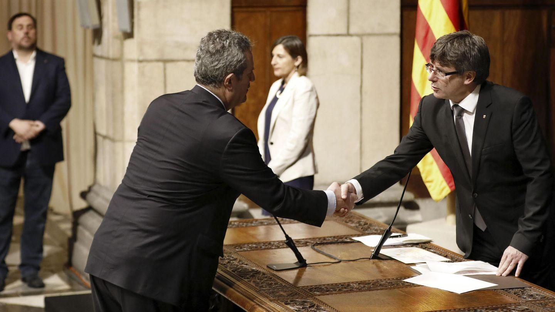 El nuevo 'conseller' de Interior, Joaquim Forn (2i), saluda al presidente de la Generalitat, Carles Puigdemont (d). (EFE)