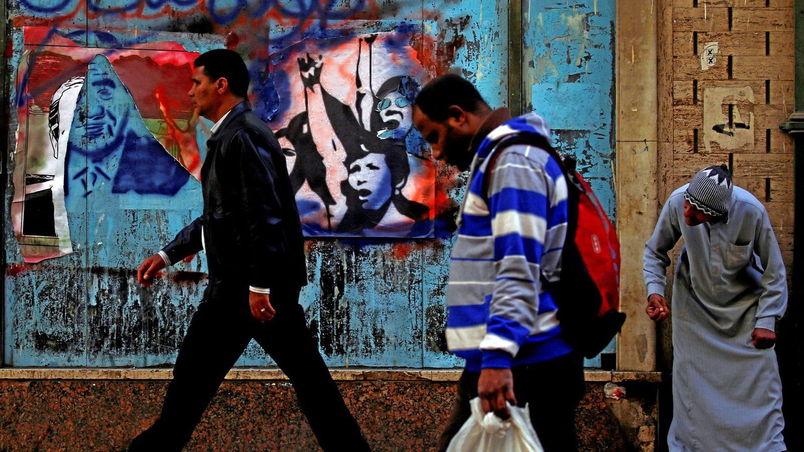 Foto: Un grupo de egipcios pasa frente a un mural con pintadas y pósteres electorales en El Cairo, el 8 de febrero de 2018. (Reuters)