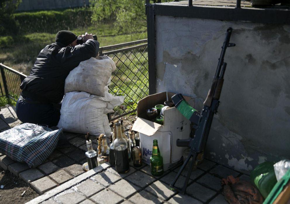 Foto: Un prorruso armado custodia un puesto de control en una vía férrea cercana a Slaviansk, en el este de Ucrania (Reuters).