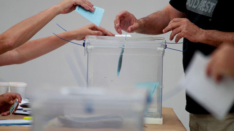 Foto: Un miembro de una mesa electoral recoge papeletas de una urna durante las elecciones. (Reuters)