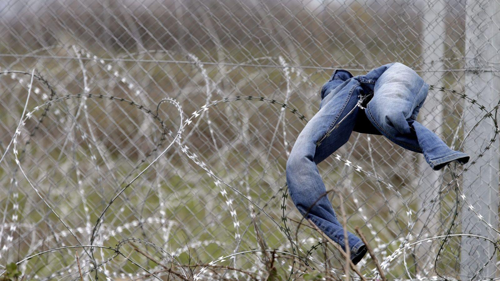 Foto: Unos pantalones vaqueros cuelgan de la alambrada que delimita Grecia con Macedonia en el campo de Idomeni.