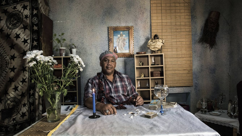 Foto: El santero cubano Fidel Revilla, en su mesa de consultas de la Santería Okántomy. (Natalia Lázaro Prevost)
