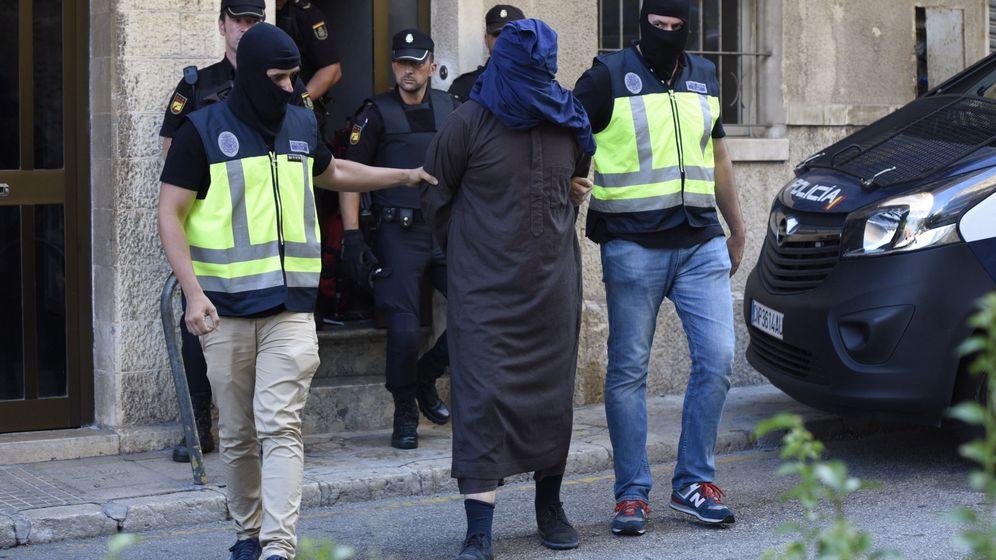 Foto: Efectivos de la Policia trasladan a un hombre detenido en la localidad de Inca (Mallorca). (EFE)