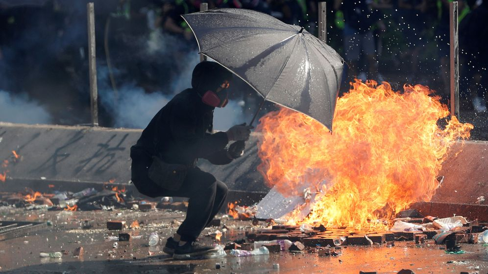 Foto: Un manifestante se protege bajo un paraguas durante el caos de las protestas. (REUTERS)