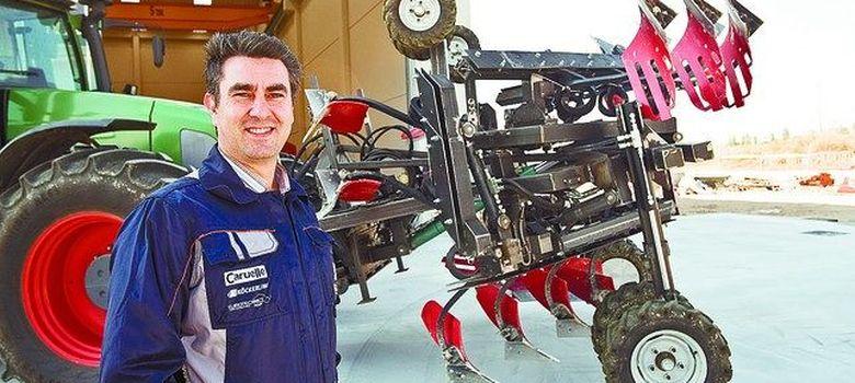 Foto: Julio Santamaría posa delante del prototipo de arado hidráulico. (Fotografía: Diario de Burgos)