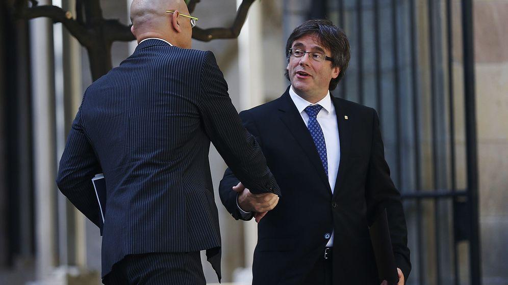 Foto: Carles Puigdemont saluda al 'conseller' de Exteriores, Raül Romeva. (EFE)