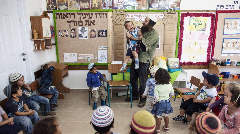 Natanel, un profesor, juega con un niño en la colonia de Havat Gilad, al sur de Nablús, en Cisjordania (Reuters).
