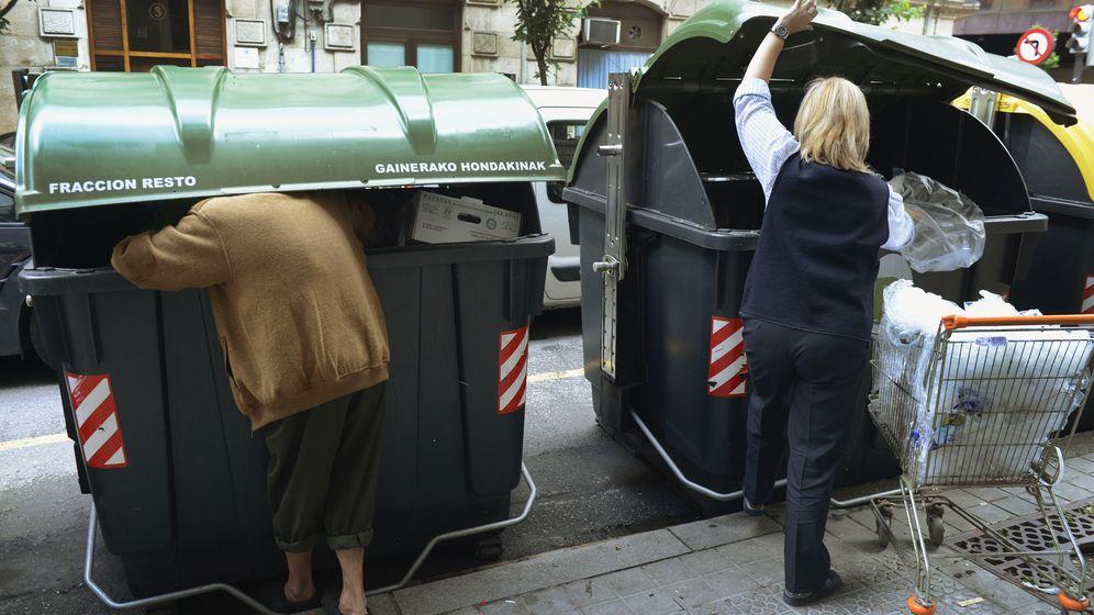 Foto: Un hombre busca comida en un contenedor de Bilbao mientras un empleado de un supermercado tira comida en el de al lado. (Reuters)