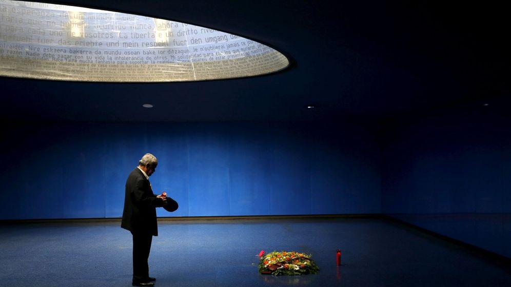 Foto: Un hombre enciende una vela en el monumento a las víctimas del 11-M. (Reuters)