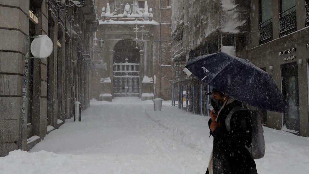 Foto: Viandantes caminan sobre la nieve en el centro de Madrid. (EFE)