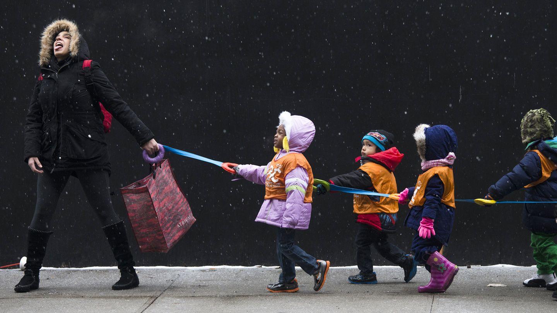 Una profesora de guardería conduce a sus alumnos por una calle de Harlem, Nueva York (Reuters).