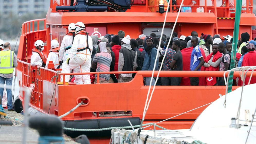 Foto: Agentes de la Policía Nacional, Guardia Civil y voluntarios de Cruz Roja ayudan a desembarcar en el puerto de Arguineguín (Gran Canaria). (EFE)