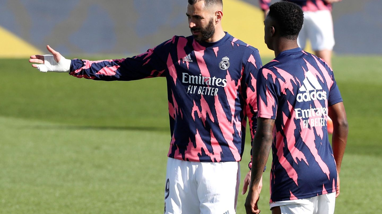 Benzema habla con Vinícius antes de un partido del Real Madrid. (EFE)