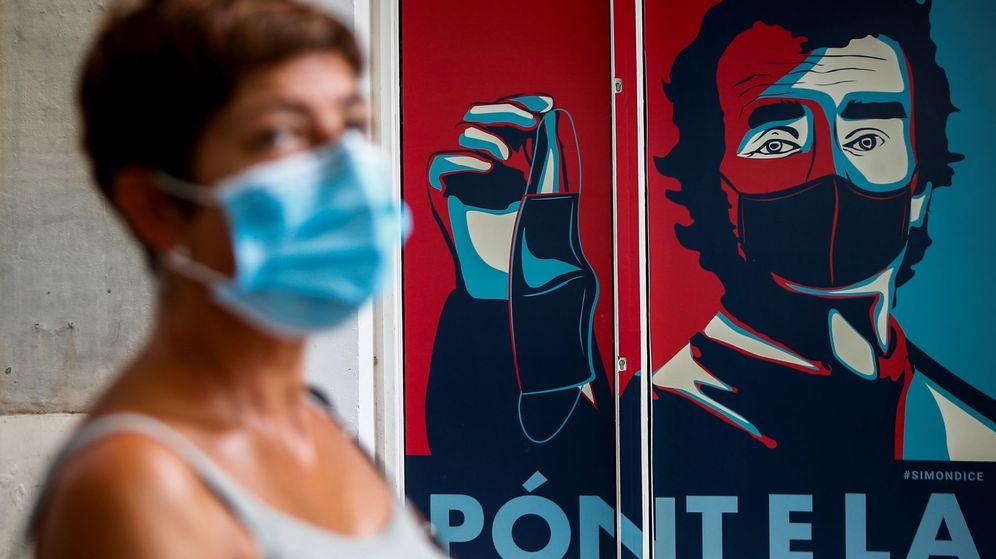 Foto: Un graffiti con la imagen del director del centro de Coordinación de Alertas y Emergéncias Sanitarias, Fernando Simón, preside la entrada de un comercio del barrio del Eixample de Barcelona. (EFE)