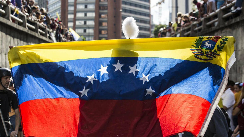 Una persona extiende una bandera venezolana durante un homenaje a los fallecidos en las protestas, en Caracas, el 24 de julio de 2017. (EFE)