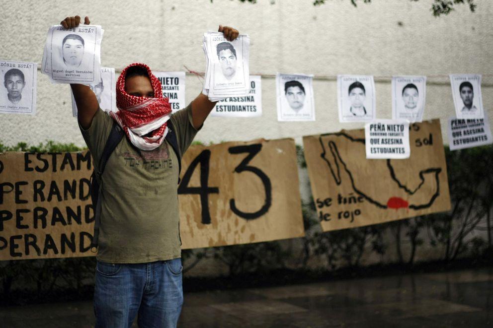 Un manifestante con fotos de Raul Isidro Burgos, estudiante desaparecido en Guerrero (Reuters).