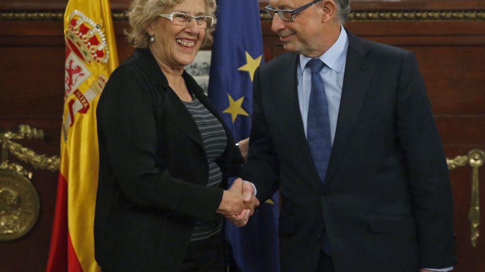Foto: El ministro de Hacienda, Cristóbal Montoro, saluda a la alcaldesa de Madrid, Manuela Carmena, en un encuentro en el ministerio hace un año. (EFE)