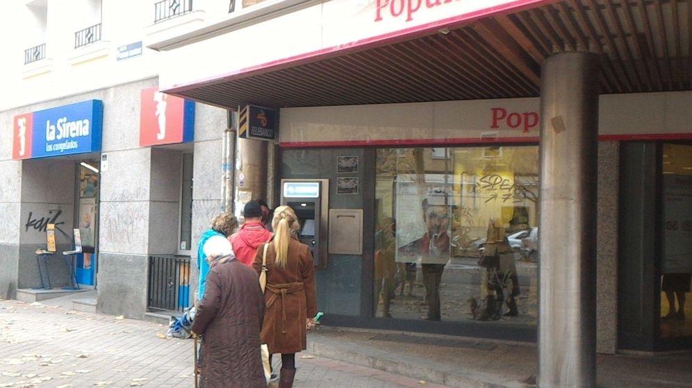Foto: Colas de clientes de ING pasa sacar dinero de un cajero de Banco Popular esta mañana en Madrid. (EC)