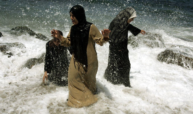 Foto: Tres mujeres se refrescan en la orilla de una playa de Argel (Reuters).