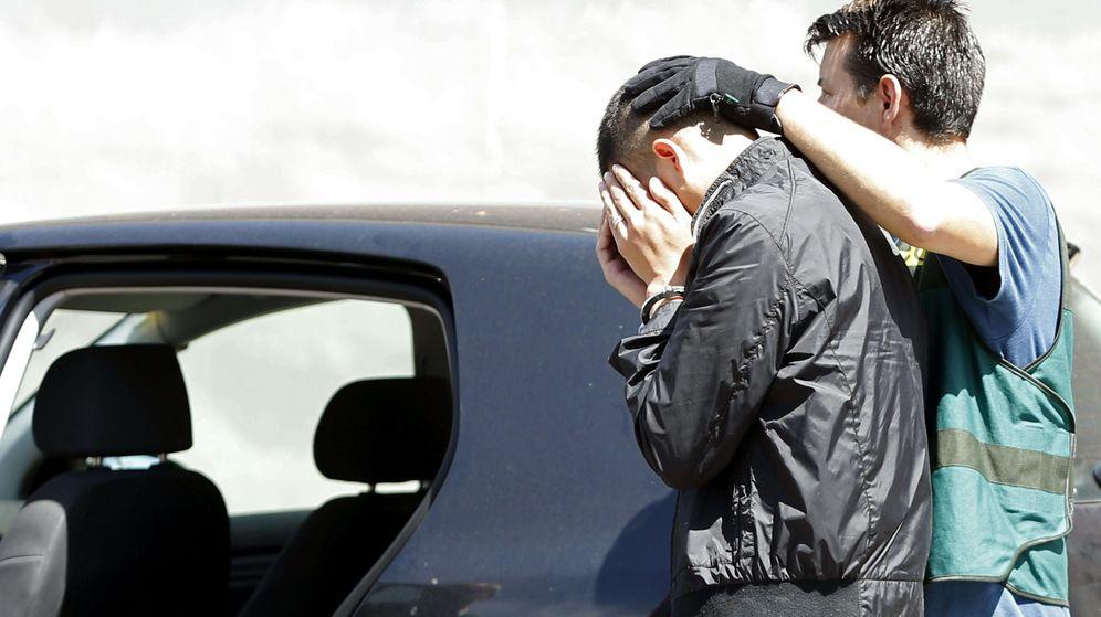 Foto: Un agente escolta a uno de los detenidos en la operación. (EFE)