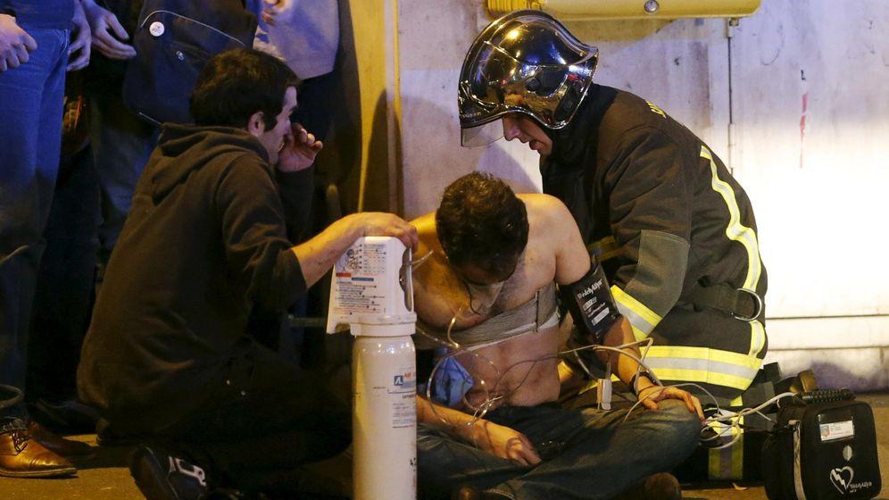 Foto: Un bombero atiende a uno de los heridos en los atentados de París. (Reuters)