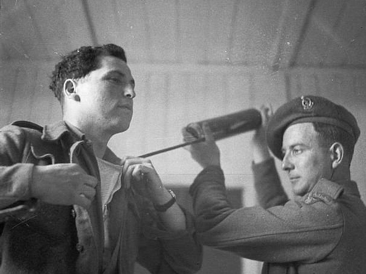 Foto: Un oficial espolvorea a un militar DDT, tras la liberación del campo de concentración de Bergen-Belsen, en 1945. (Wikimedia Commons)