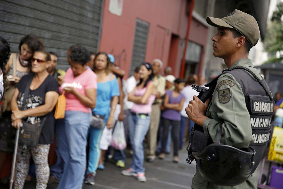 Foto: Un soldado venezolano vigila una cola de personas que esperan para comprar harina de maíz y margarina, en Caracas, el 15 de marzo de 2016. (Reuters)