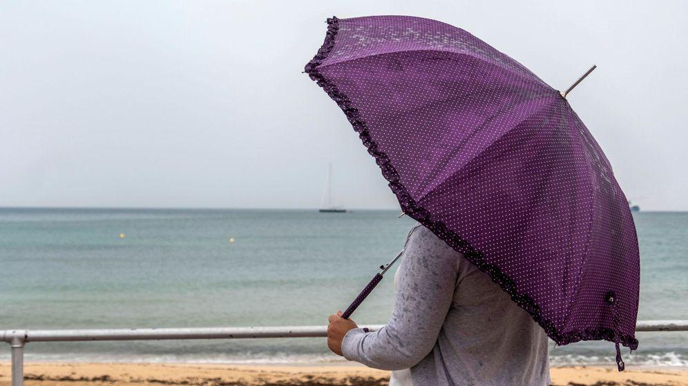 Foto: Una mujer se protege de la lluvia en Palma de Mallorca. (Efe)