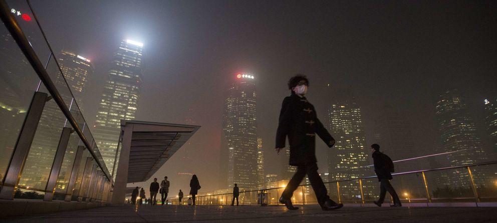 Foto: Un hombre con mascarilla camina por el distrito financiero de Shanghái bajo un manto de polución (Reuters).
