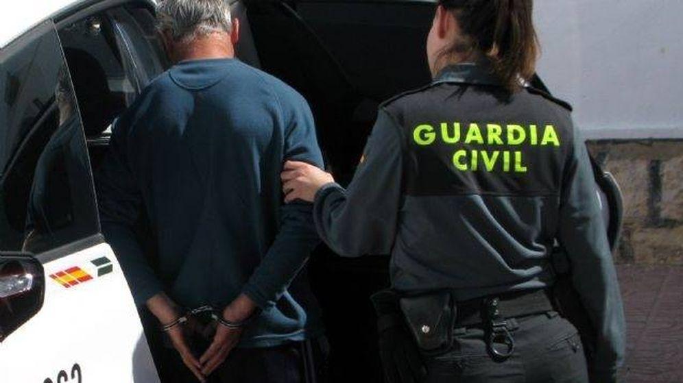 Foto: Una agente de la Guardia Civil conduce a un detenido al interior de un vehículo. (EFE)