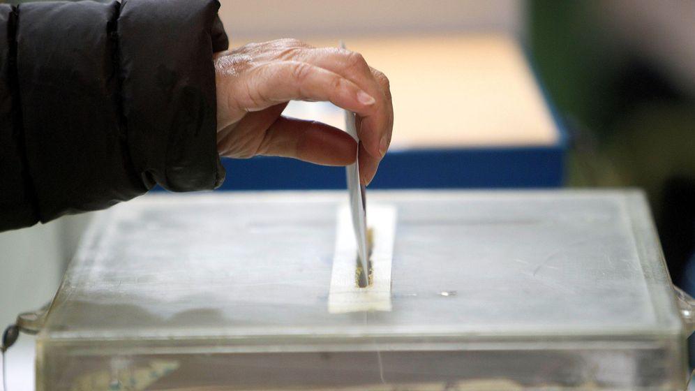Foto: Una persona deposita una papeleta en un colegio electoral en Vigo. (EFE)