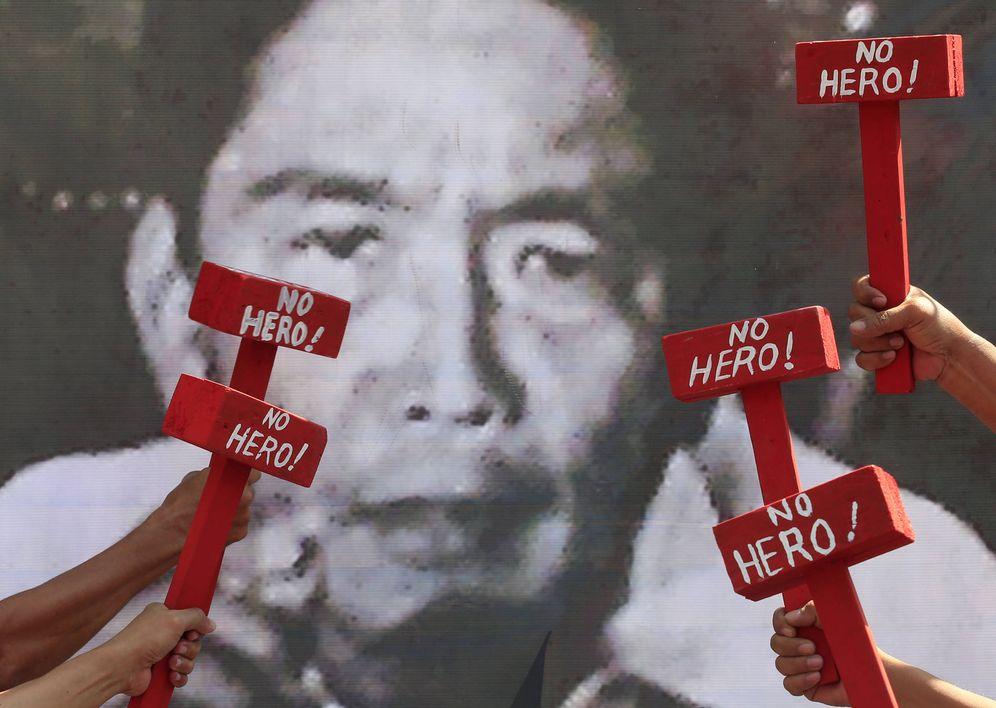 Foto: Protesta frente a un retrato de Ferdinand Marcos por el enterramiento del ex dictador en el Cementerio de los Héroes de Manila, en noviembre de 2016. (Reuters)