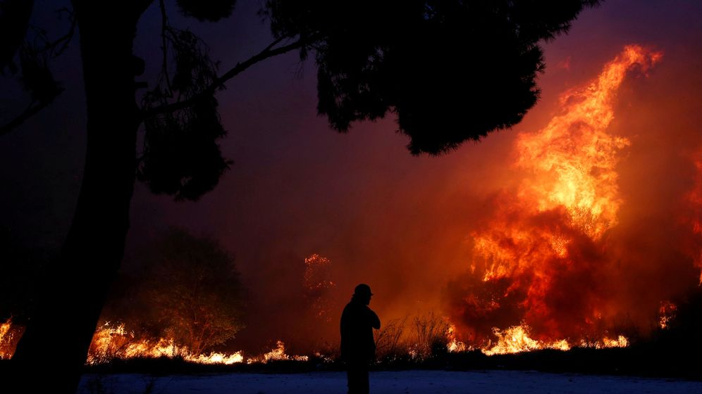 Foto: A man looks at the flames as a wildfire burns in the town of rafina