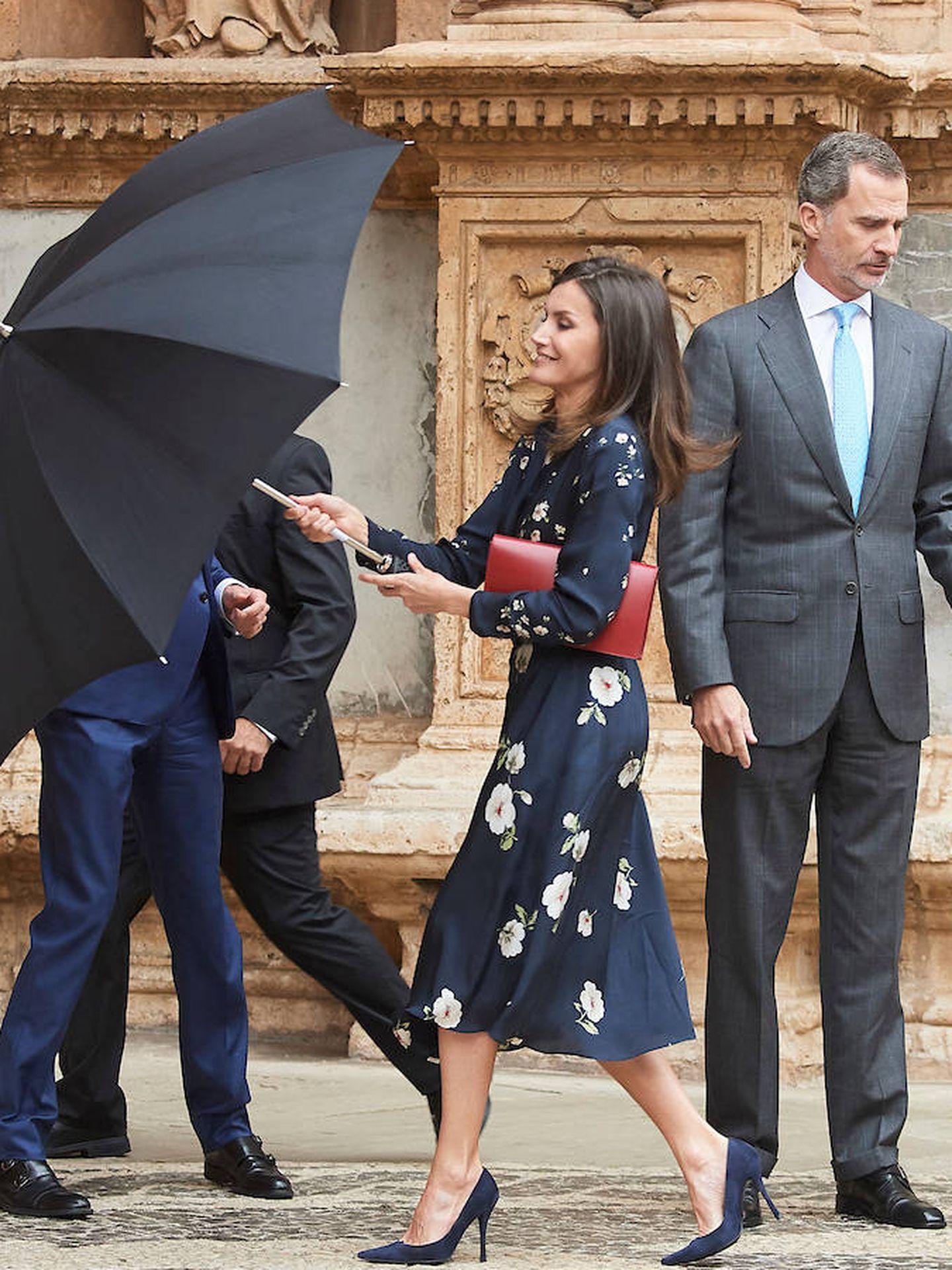 La Reina abre el paraguas para resguardarse de la lluvia. (Limited Pictures)
