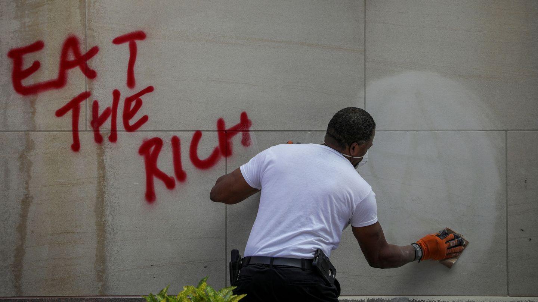 Una persona limpia un grafiti donde pone 'Comerse a los ricos'. (Reuters)