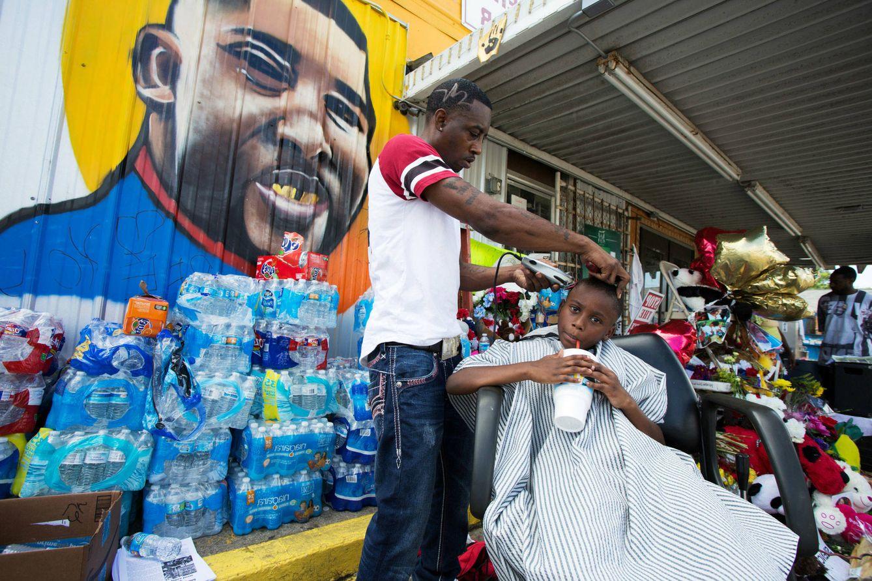 """Foto: Un afroamericano ofrece """"cortes de pelo por la justicia"""" ante un memorial improvisado por Alton Sterling, muerto a manos de la policía en Luisiana, en julio de 2016 (Reuters)"""